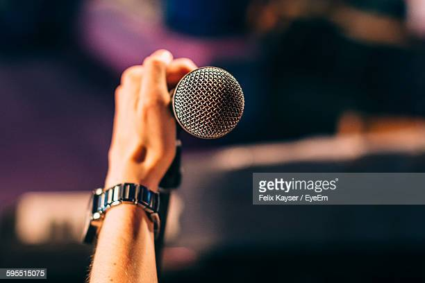 cropped hand of musician holding microphone - chanteur photos et images de collection