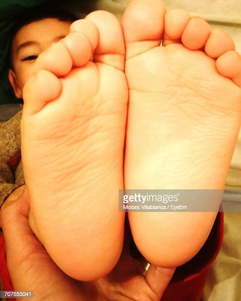 Cropped Hand Of Parent Holding Son Feet At Home