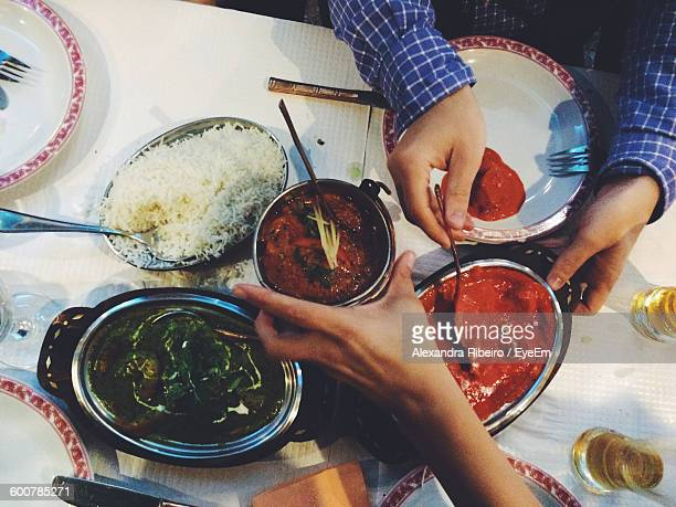 Cropped Hand Of People Having Indian Food At Restaurant