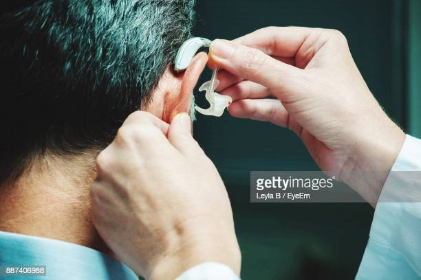 cropped hand of person adjusting man hearing aid - assistive technology stock photos and pictures