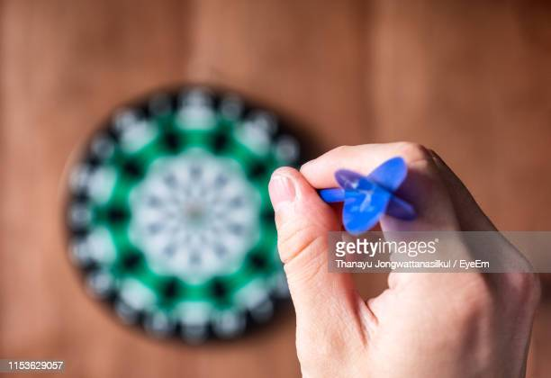 cropped hand of person aiming dart at dartboard - dartboard stock pictures, royalty-free photos & images