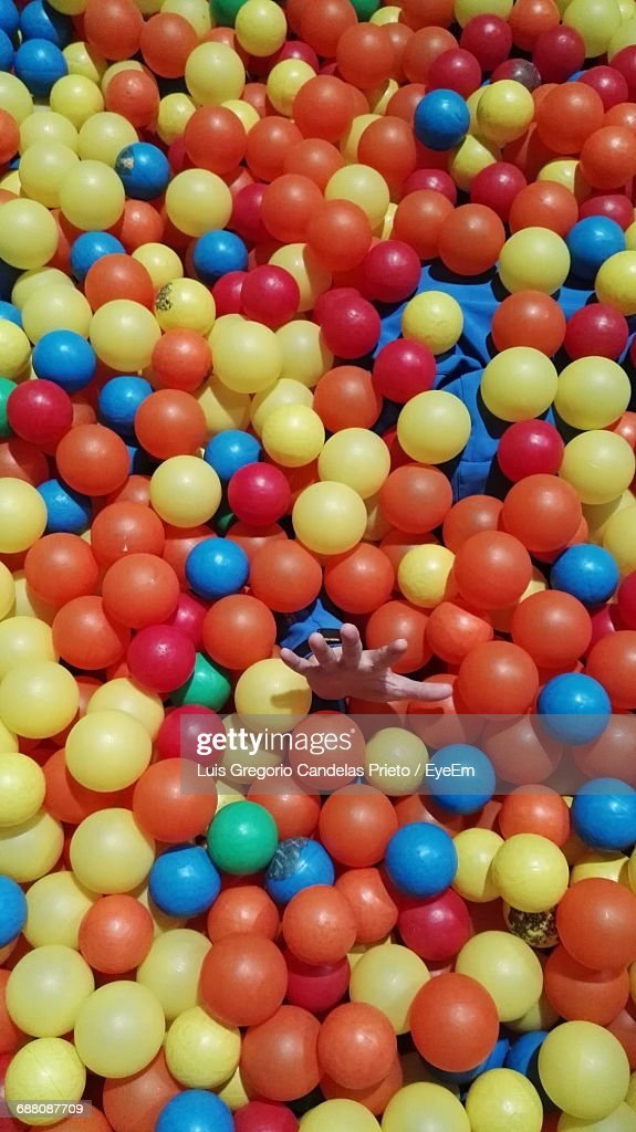 Cropped Hand Of Person Amidst Colorful Ball Pool : Stock Photo