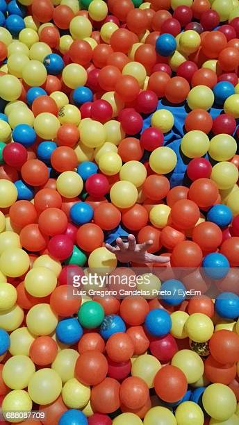 Cropped Hand Of Person Amidst Colorful Ball Pool