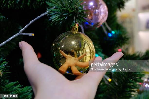 Cropped Hand Of Person By Christmas Decoration
