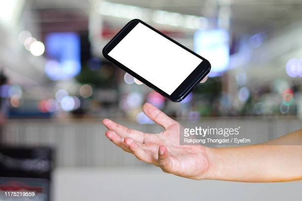cropped hand of person catching mobile phone - catching stock pictures, royalty-free photos & images