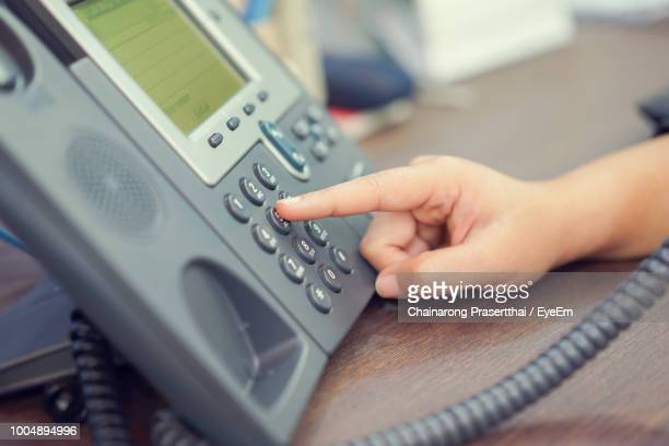 cropped hand of person dialing telephone keypad on table - dial stock pictures, royalty-free photos & images