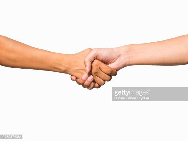 cropped hand of person doing handshake against white background - handshake stock pictures, royalty-free photos & images