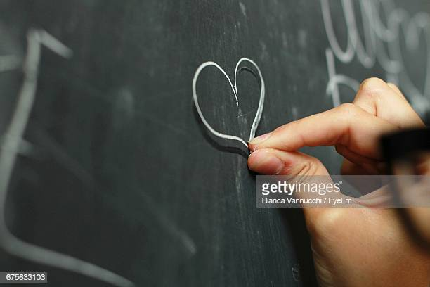 Cropped Hand Of Person Drawing Heart Shape On Blackboard