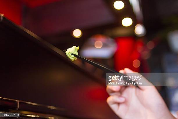 Cropped Hand Of Person Eating Wasabi With Chopsticks