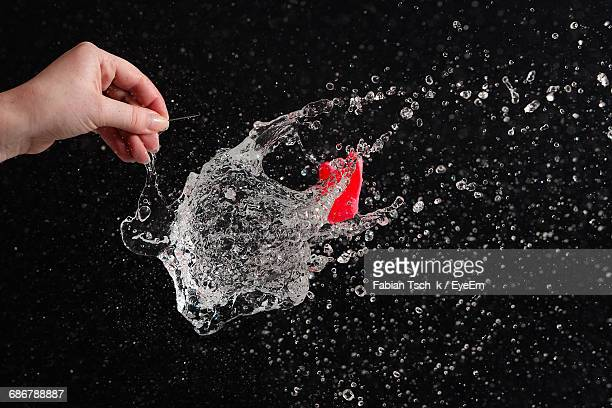 Cropped Hand Of Person Exploding Water Bomb Against Black Background