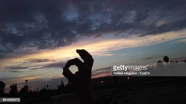 Cropped Hand Of Person Gesturing Against Sky During Sunset
