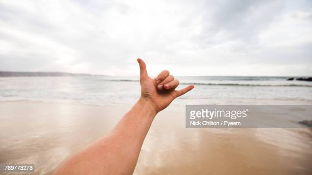 Cropped Hand Of Person Gesturing Shaka Sign Against Sky