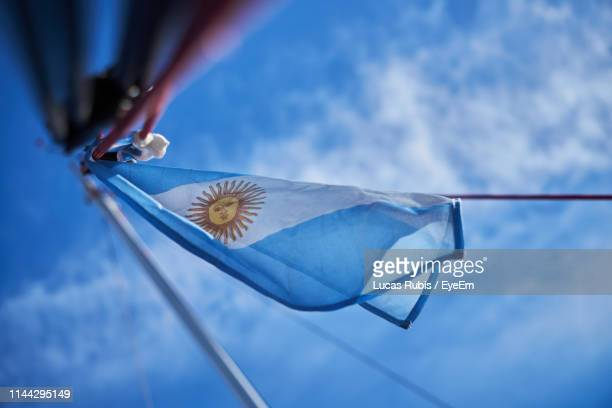 cropped hand of person gesturing towards argentina flag against blue sky - argentinas flagga bildbanksfoton och bilder