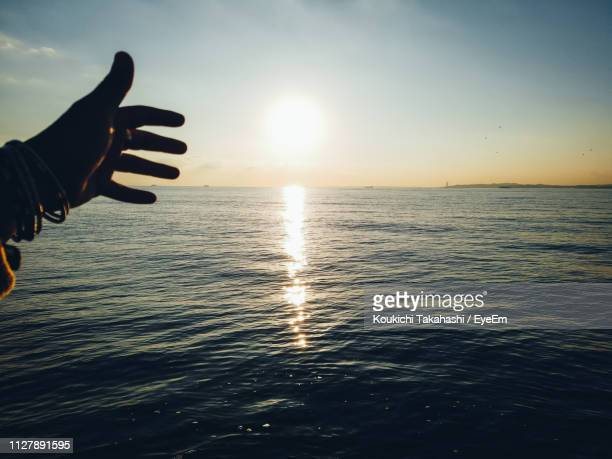 Cropped Hand Of Person Gesturing Towards Sea Against Sky During Sunset