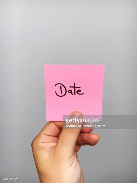 Cropped Hand Of Person Holding Adhesive Note With Date Text Against Gray Background