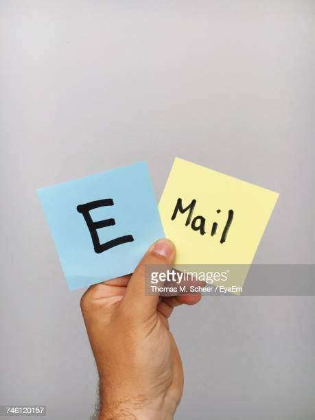 Cropped Hand Of Person Holding Adhesive Notes With E-Mail Text Against Gray Background