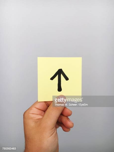 Cropped Hand Of Person Holding Arrow Symbol On Adhesive Note Against Gray Background