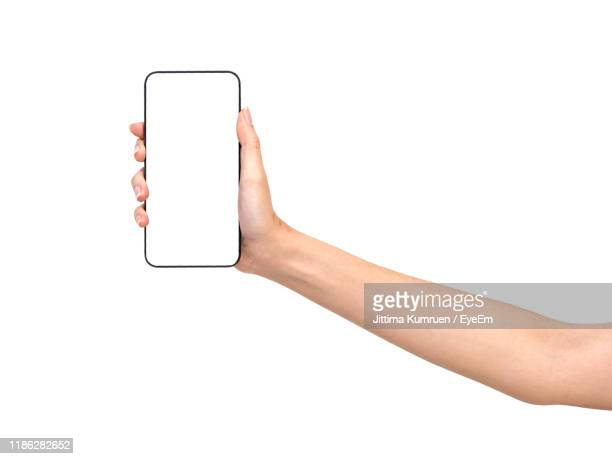 cropped hand of person holding blank smart phone against white background - vasthouden stockfoto's en -beelden