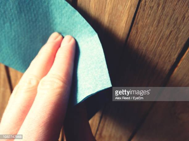 Cropped Hand Of Person Holding Blue Paper On Wooden Table