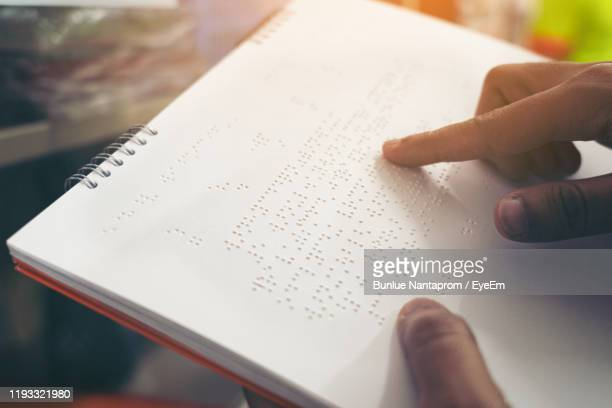 cropped hand of person holding book with braille language indoors - braille stock pictures, royalty-free photos & images