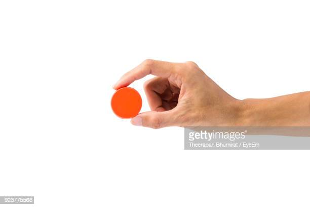 cropped hand of person holding bottle cap against white background - cap stock pictures, royalty-free photos & images