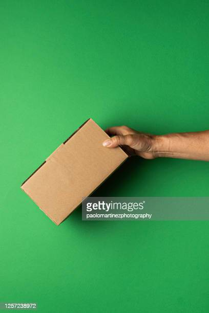 cropped hand of person holding box against green background - carton stock pictures, royalty-free photos & images