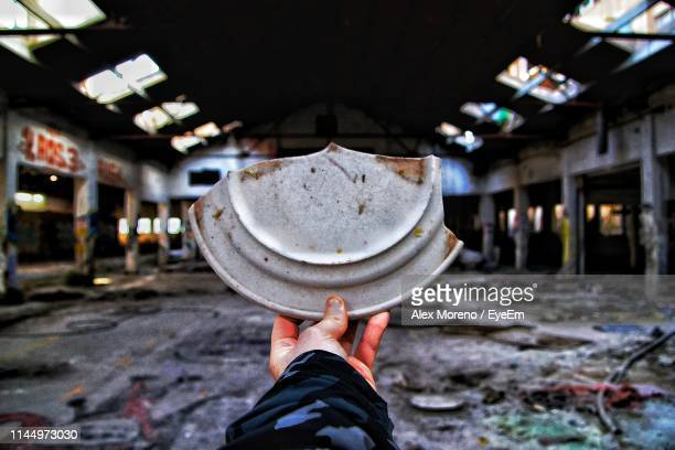 cropped hand of person holding broken plate in abandoned building - human body part stock pictures, royalty-free photos & images