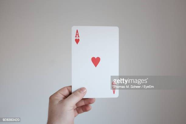 Cropped Hand Of Person Holding Cards Against Wall