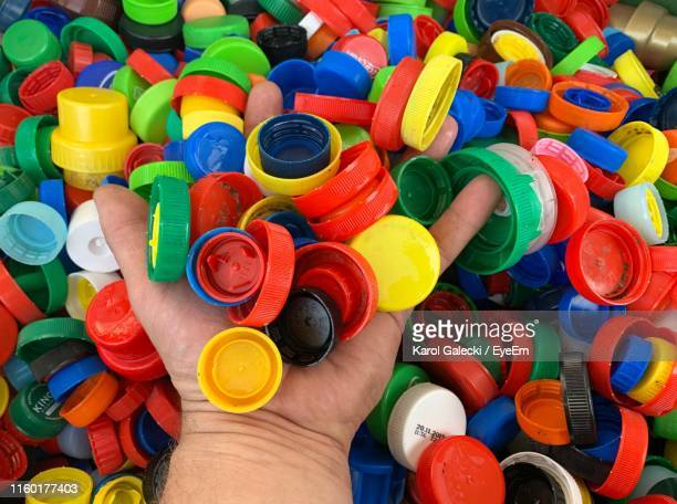 Cropped Hand Of Person Holding Colorful Bottle Caps