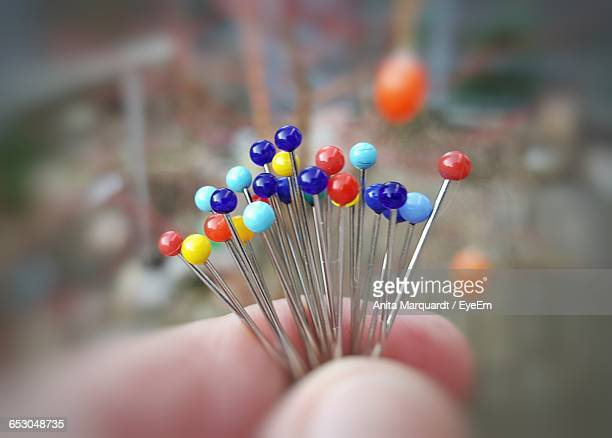 Cropped Hand Of Person Holding Colorful Straight Pins