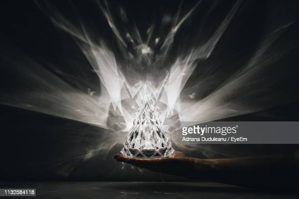 cropped hand of person holding crystal in darkroom - crystal stock pictures, royalty-free photos & images