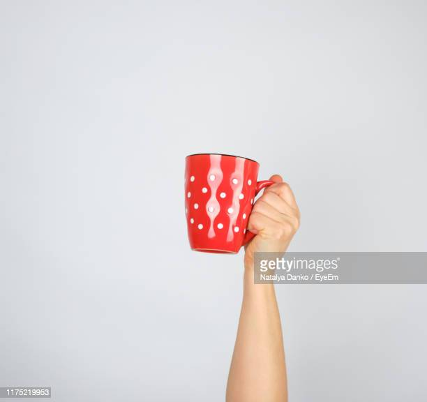 cropped hand of person holding cup against white background - mug stock pictures, royalty-free photos & images