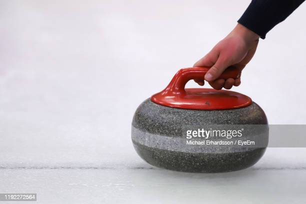 cropped hand of person holding curling stone on ice - curling sport stock pictures, royalty-free photos & images