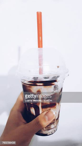 Cropped Hand Of Person Holding Drink In Glass Against White Background