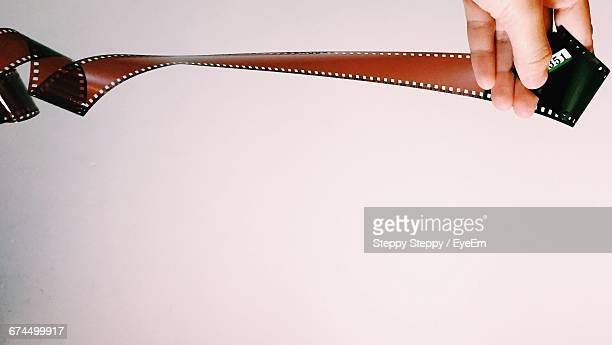 Cropped Hand Of Person Holding Film Reel Against White Background