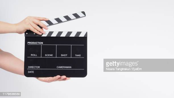 cropped hand of person holding film slate over white background - clapboard stock pictures, royalty-free photos & images