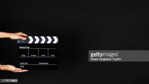 cropped hand of person holding film slate with text against black background - clapboard stock pictures, royalty-free photos & images