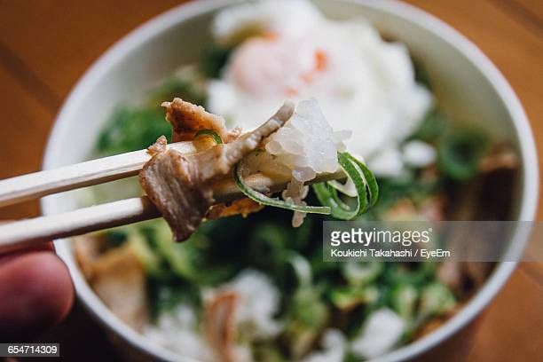Cropped Hand Of Person Holding Food In Chopsticks Against Bowl
