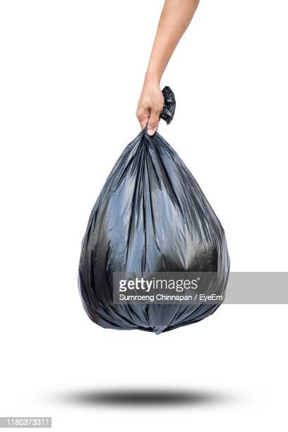 cropped hand of person holding garbage bag against white background - bin bag stock pictures, royalty-free photos & images