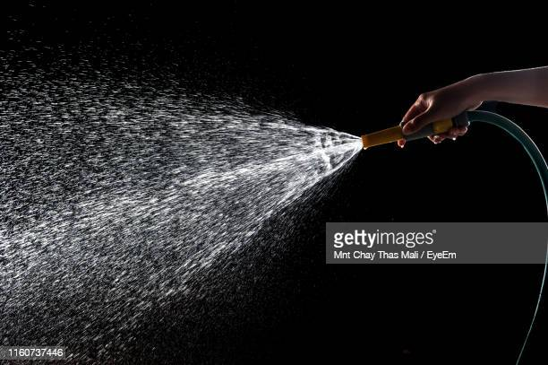 cropped hand of person holding garden hose against black background - spraying stock pictures, royalty-free photos & images
