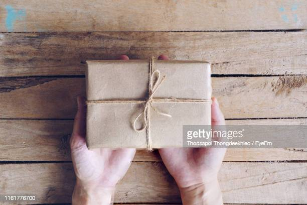 cropped hand of person holding gift box on table - brown paper stock pictures, royalty-free photos & images