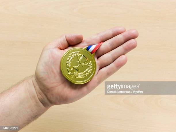 cropped hand of person holding gold medal over wooden table - medalhista - fotografias e filmes do acervo