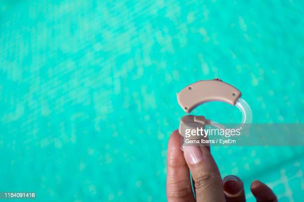 cropped hand of person holding hearing aid over swimming pool - ear canal stock-fotos und bilder
