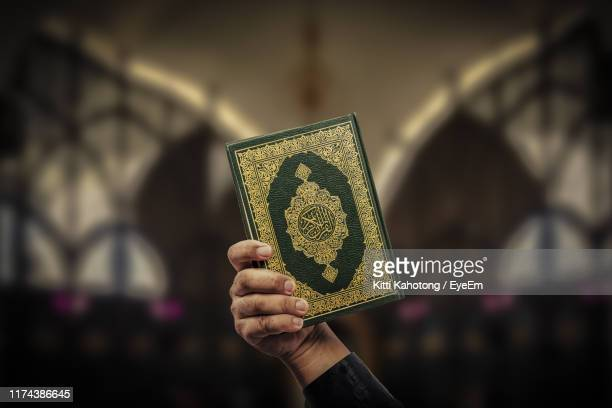 cropped hand of person holding holy book - koran stock pictures, royalty-free photos & images