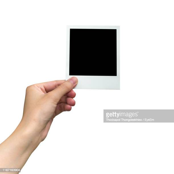 cropped hand of person holding image print transfer against white background - polaroid stock pictures, royalty-free photos & images