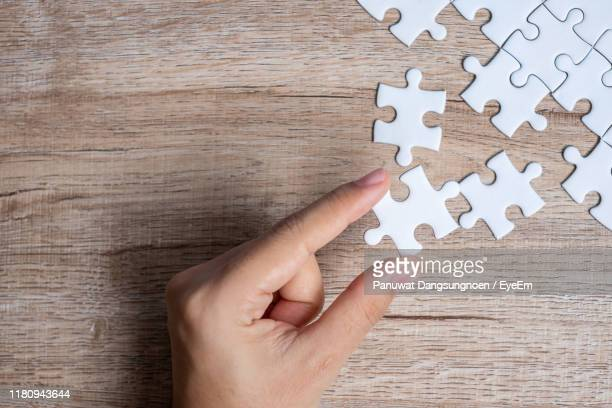 cropped hand of person holding jigsaw piece on table - パズル ストックフォトと画像