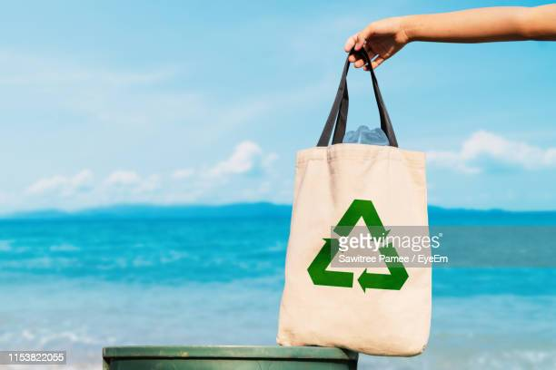 cropped hand of person holding leather bag with recycling symbol on garbage bin against sea - ゴミ袋 ストックフォトと画像