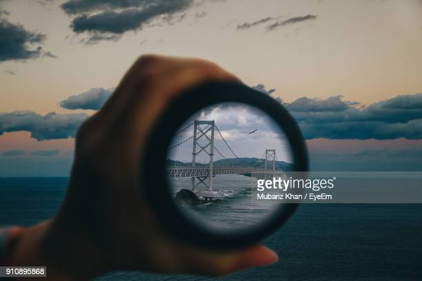 Cropped Hand Of Person Holding Lens With Reflection Of Bridge Against Sky
