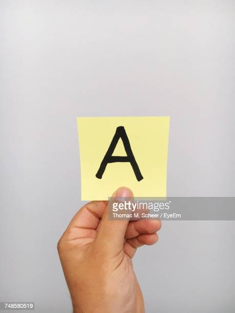 Cropped Hand Of Person Holding Letter A On Adhesive Note Against Gray Background