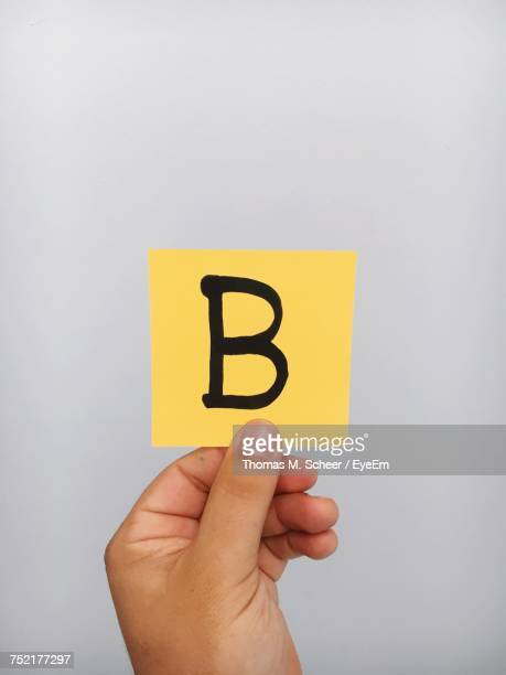 cropped hand of person holding letter b on adhesive note against gray background - letra b imagens e fotografias de stock